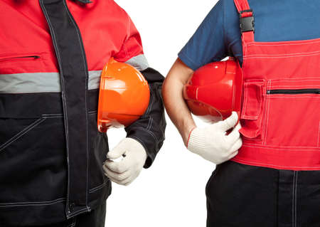 Two builders or industrial workers in uniform holding hardhats isolated on white photo