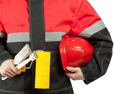 Construction worker in uniform holding hardhat, paint roller and brushes; painter with tools isolated on white photo