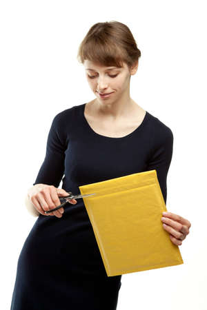 Attractive young woman cutting envelope parcel package; young woman opening post envelope isolated on white photo