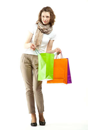 Fashionable young woman doing shopping; full length portrait of an attractive young woman with multicolored paper bags isolated on white Stock Photo - 12752614