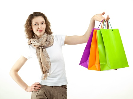 Closeup portrait of attractive young woman with multicolored paper bags isolated on white; shopping concept photo