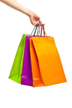 Mano sosteniendo bolsas de papel multicolores aislados en blanco, concepto de compras Foto de archivo
