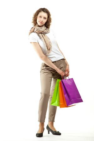 Fashionable young woman doing shopping; full length portrait of an attractive young woman with multicolored paper bags isolated on white  photo