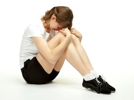 Attractive young woman sitting on the floor in sport clothes; white background