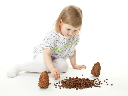 cute baby girl: Cute baby girl playing with cedar cones on white background