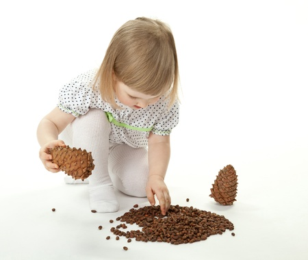 Cute baby girl playing with cedar cones on white background Stock Photo - 12906560