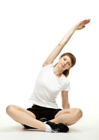 sport clothes: Attractive young woman sitting on the floor in sport clothes and doing sport exercises; white background  Stock Photo