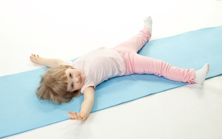 Cute baby girl doing sport exercises lying on the floor; isolated on white photo