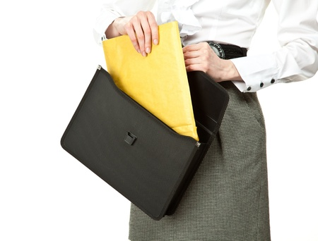 Businesswoman taking letter out of briefcase (or putting letter into briefcase); woman's hands holding briefcase and documents isolated on white Stock Photo - 12906733