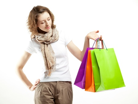 Beautiful young woman holding multicolored paper bags on white background; shopping concept photo
