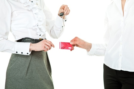 buying real estate: Concept of buying real estate: women exchanging keys and plastic card; isolated on white