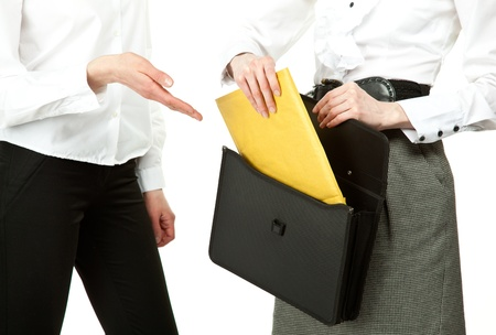 Business people exchanging documents; closeup of businesswomen's hands holding envelope/document/file; isolated on white background Stock Photo - 12906723