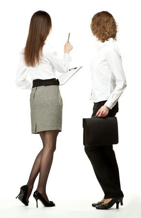 Young businesswomen at a business meeting/negotiations/conference/presentation; rear view of two businesswomen holding briefcase and clipboard and showing something with a pen, full length portrait white background
