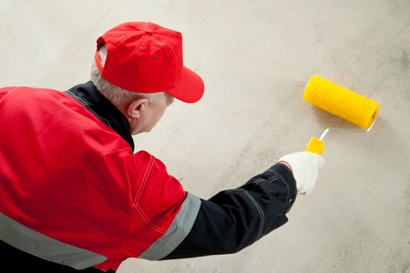 Painter at workplace; painter working against the concrete wall photo