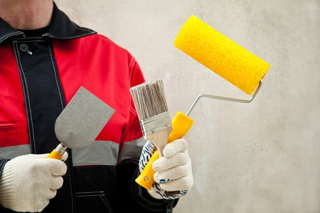 Construction worker in uniform at workplace holding paint roller and brushes; painter with tools photo