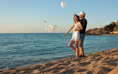 Happy playful young couple with balloons having fun at sunny beach; joyful young couple at summer vacation  photo