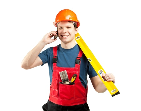Cheerful construction worker in uniform and hardhat with special tools and mobile phone; studio shot illustrating construction services; isolated on white photo