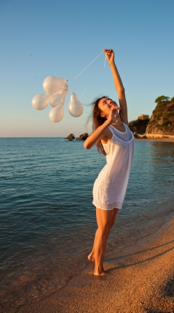 sincere girl: Happy smiling brunette girl with white balloons on sunny beach; summer vacation at Mediterranean Sea