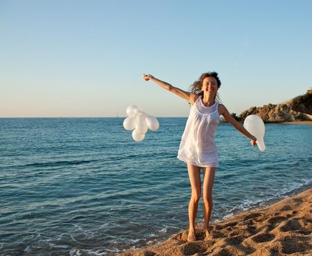 chica surf: Feliz sonriente ni�a morena con globos blancos en la playa soleada; mujer joven y atractiva disfrutando de las vacaciones de verano en el mar