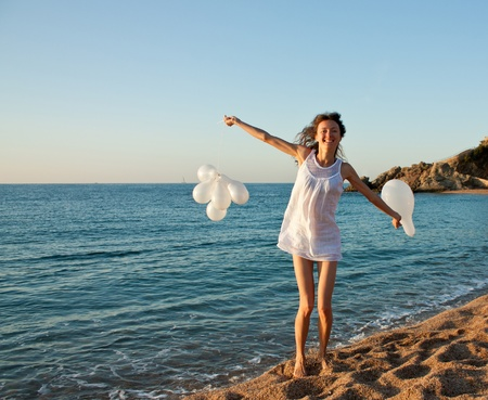 woman beach dress: Happy smiling brunette girl with white balloons on sunny beach; attractive young woman enjoying summer vacation at the sea