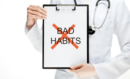 Doctor advising to abandon unhealthy habits, closeup of doctors hands holding clipboard with the word BAD HABIT, text crossed with red marker, healthy lifestyle concept isolated on white Stock Photo