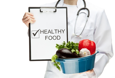 dietology: Doctor advising healthy food, closeup of doctors hands holding clipboard with marked checkbox with the word HEALTHY FOOD, and brazier with fresh vegetables, healthy eating concept isolated on white