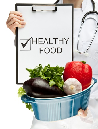dietology: Doctor advising healthy food, closeup of doctors hands holding clipboard with marked checkbox and the words HEALTHY FOOD, and brazier with fresh vegetables, healthy eating concept isolated on white