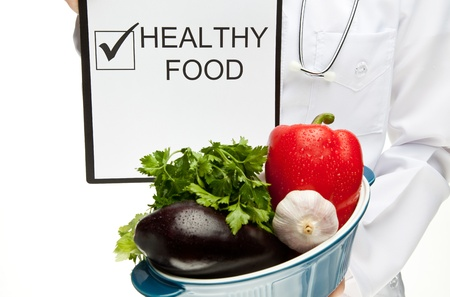 Doctor advising healthy food, closeup of doctor's hands holding clipboard with marked checkbox and words HEALTHY FOOD, and brazier with fresh vegetables, healthy eating concept isolated on white Stock Photo - 13015098