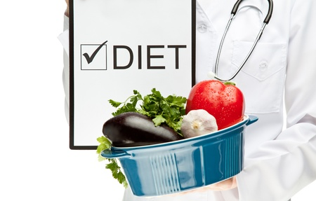 Doctor prescribing diet, closeup of doctors hands holding clipboard with marked checkbox with the word DIET and brazier with fresh vegetables, dietary concept isolated on white photo