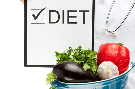 Doctor prescribing diet, closeup of doctors hands holding clipboard with marked checkbox and words DIET, and brazier with fresh vegetables, dietary concept isolated on white photo