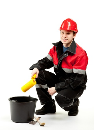 Cheerful construction worker (painter) in uniform and hardhat with special tools; studio shot on white background photo
