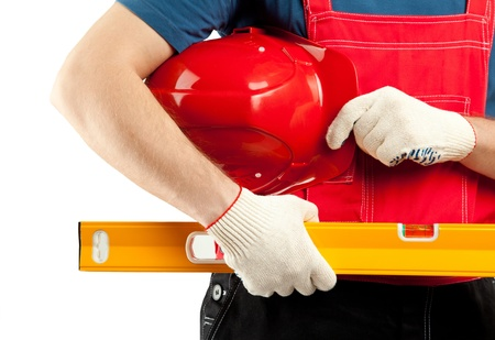 Construction worker in uniform holding hardhat and level isolated on white photo