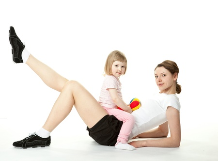 limbering: Young woman and her little daughter doing sport exercises together; white background