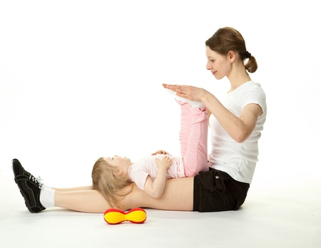 Young woman and her little daughter doing sport exercises together; white background photo