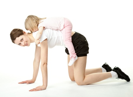 Attractive young mother and her little daughter doing sport exercises; baby girl on the back of her mother; white background photo