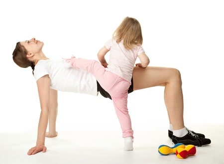 Happy young woman and her little daughter doing sport exercises together; white background Stock Photo - 13039098