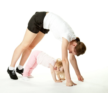 Joyful baby girl and her mother exercising; happy mother and daughter doing sport exercises together on white background photo