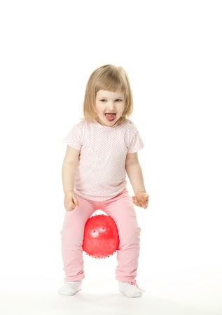 Happy laughing little girl doing exercises with a ball; white background photo