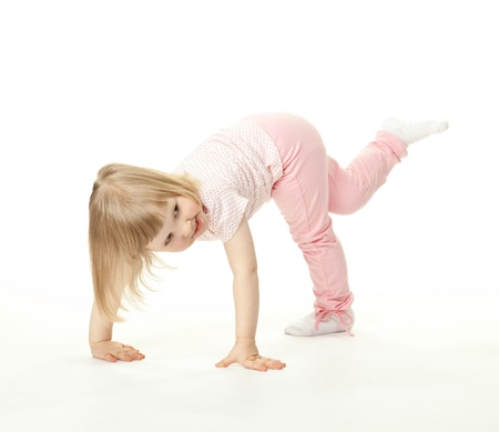 Happy adorable baby girl having fun; active child  playing on white background photo