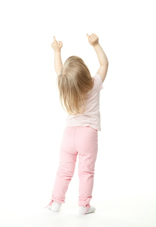 back training: Little baby girl showing something above her, rear view; white background