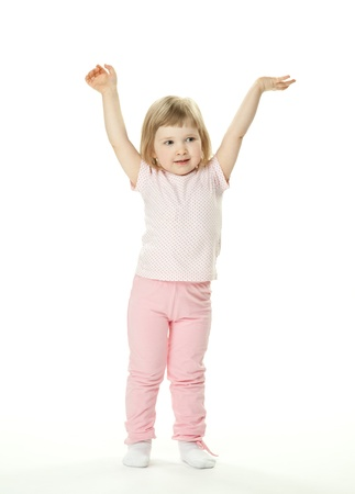 Adorable baby girl doing gymnastics; little baby girl with hands up on white background photo