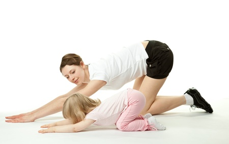 Happy young mother doing sport exercises with her little daughter; white background photo