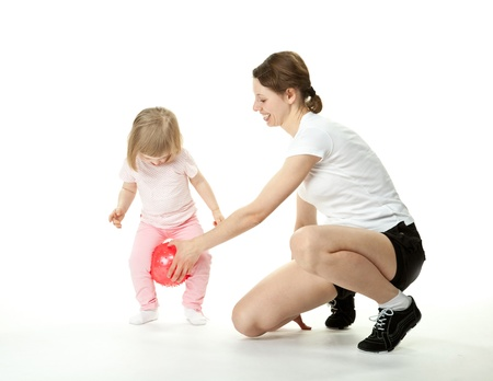 Happy laughing young mother doing sport exercises with little daughter; white background photo