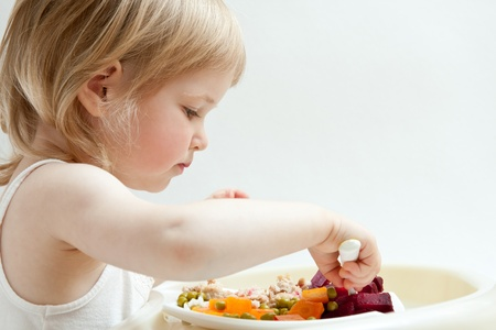 Adorable baby girl eating fresh vegetables; healthy eating for a baby photo