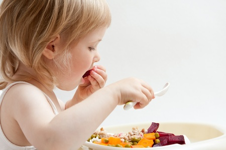 upbringing: Adorable baby girl eating fresh vegetables; healthy eating for a baby