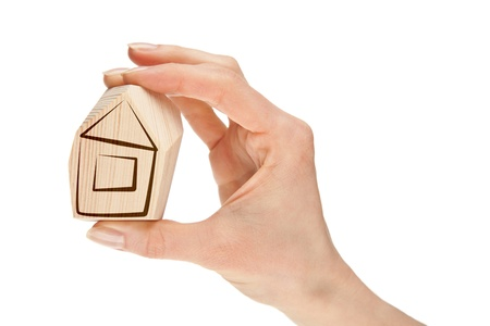 Hand holding small wooden house isolated on white; concept of buying a new house photo