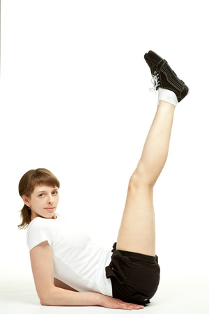 limbering: Attractive young woman sitting on the floor in sport clothes and doing sport exercises; white background  Stock Photo
