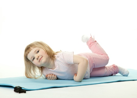 Pretty baby girl exercising lying on a training mat; white background photo