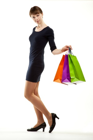 Fashionable young woman doing shopping; full length portrait of an attractive young woman with multicolored paper bags on white background