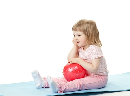 Happy baby girl doing exercises with a ball sitting on a mat; white background photo